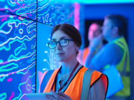 Female geologist studying graphical display of oil and gas bearing rock on screens, portrait