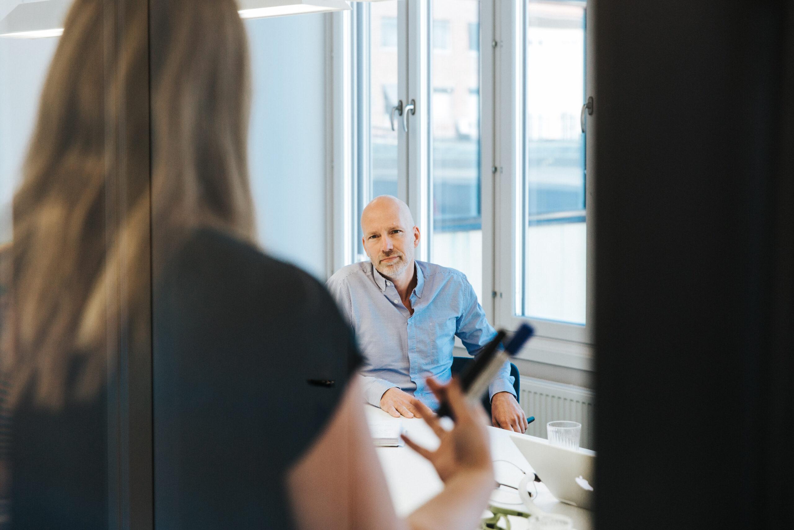 Anders Wikström sitter vid konfernsbord och lyssnar till en kollega