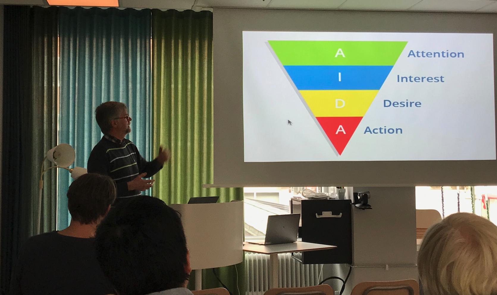 Hans Hansson presenterar framför publik, en bild på projektorduk med texten AIDA syns vid hans sida