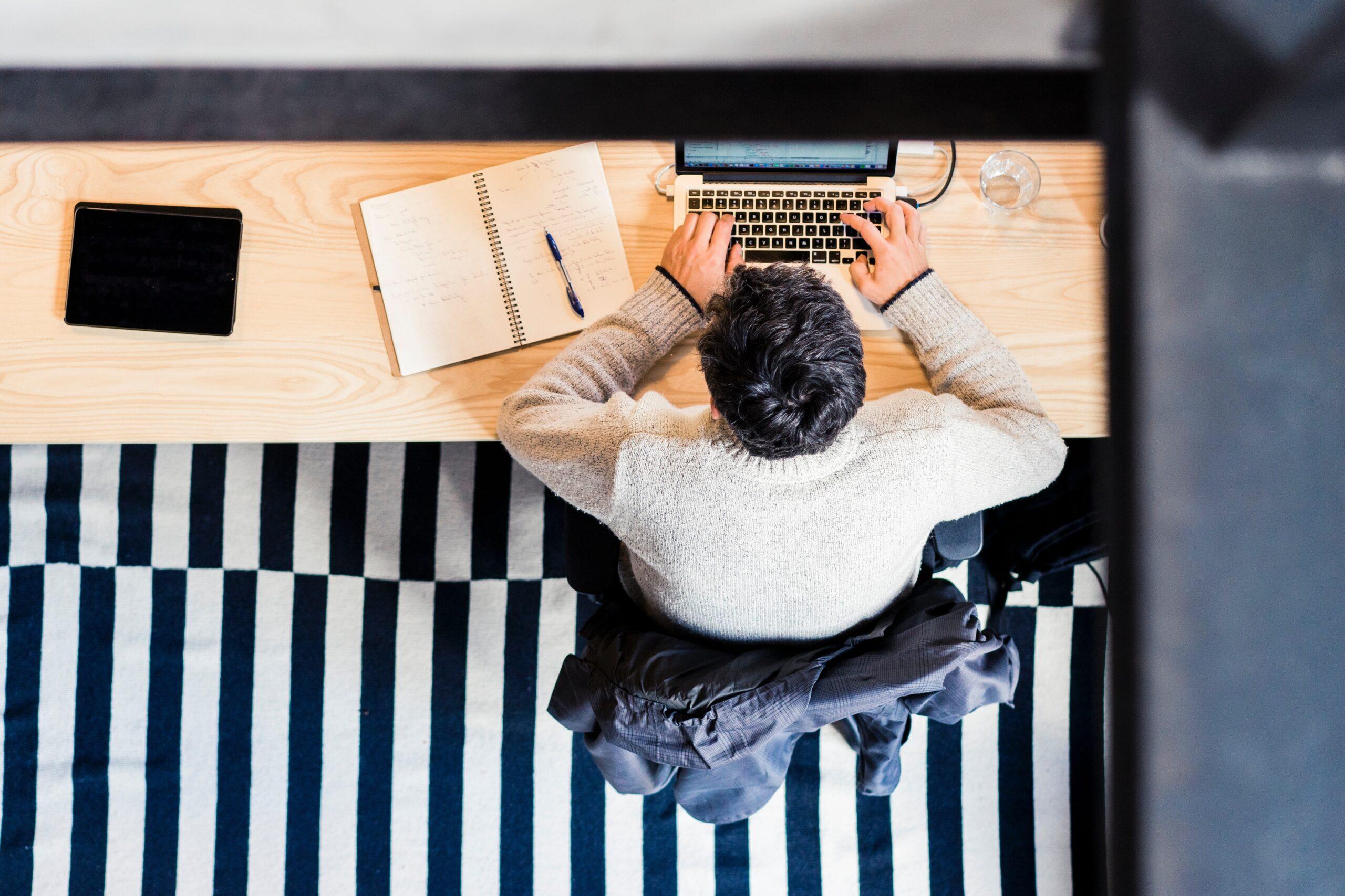 Man arbetar med laptop vid ett skrivbord, fotot taget uppifrån