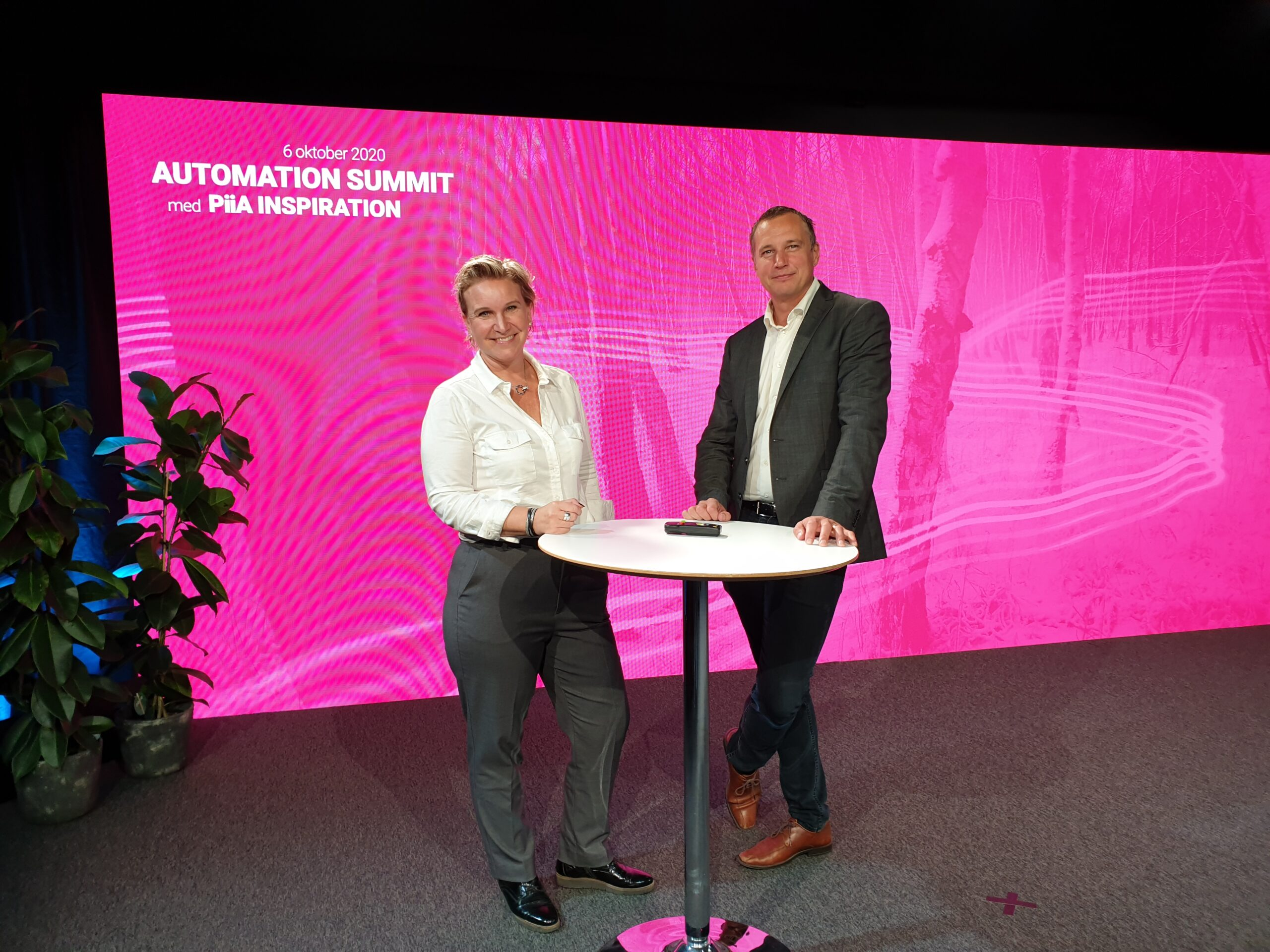 Cattis och Peter vid ett ståbord framför en stor skärm