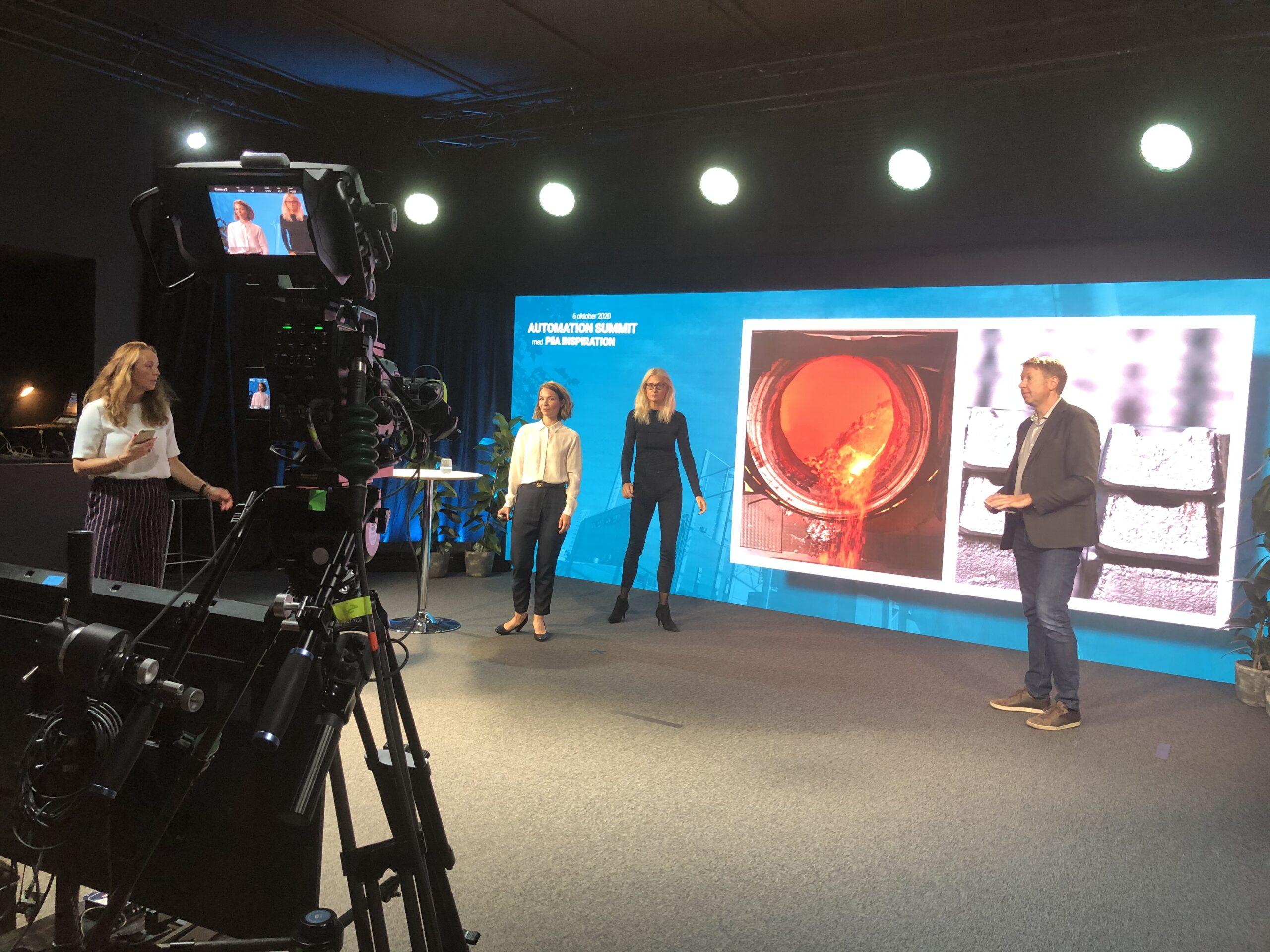 3 personer framför en stor skärm