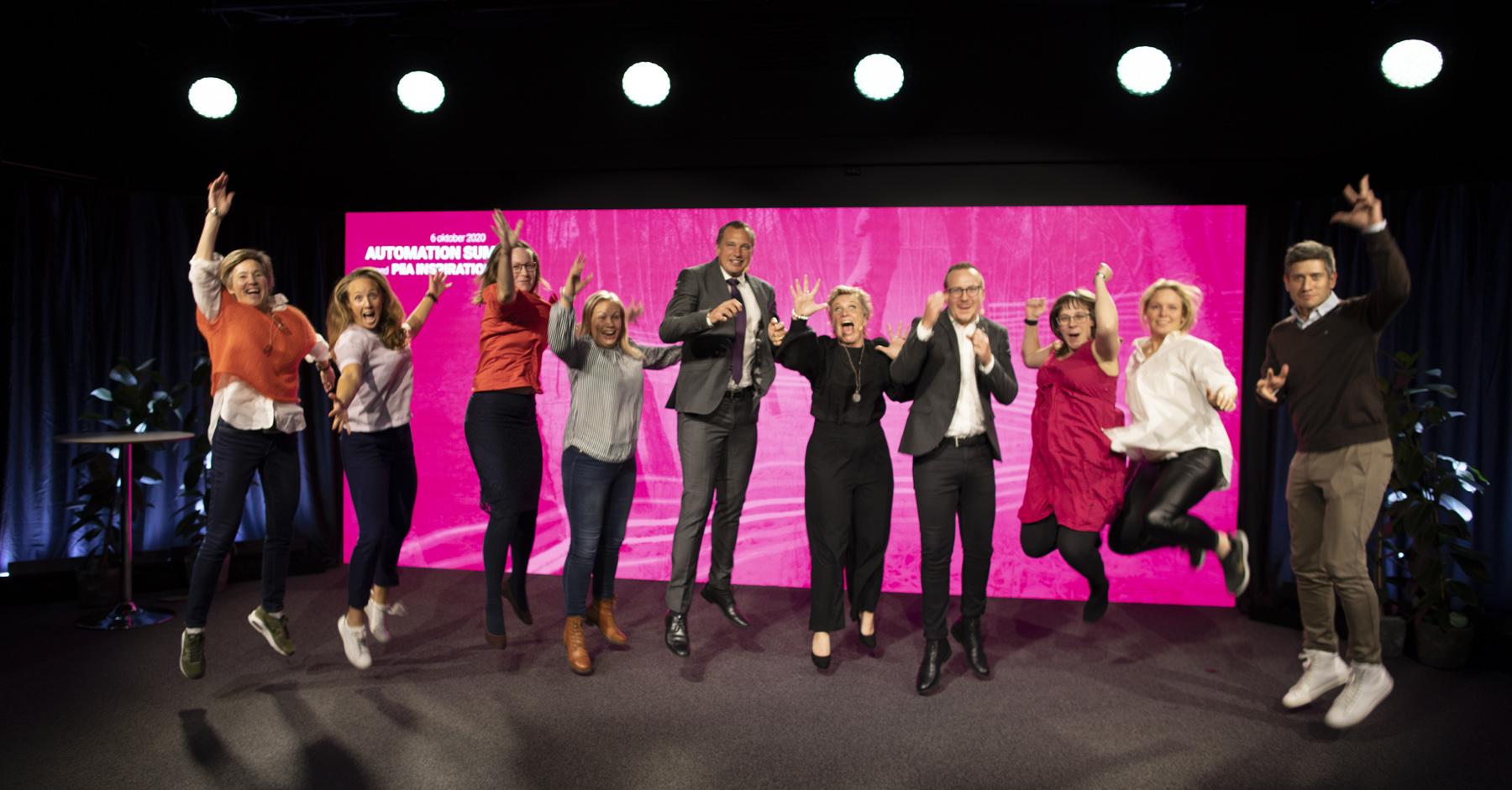 Projektteamet för konferensen hoppar glatt på scenen