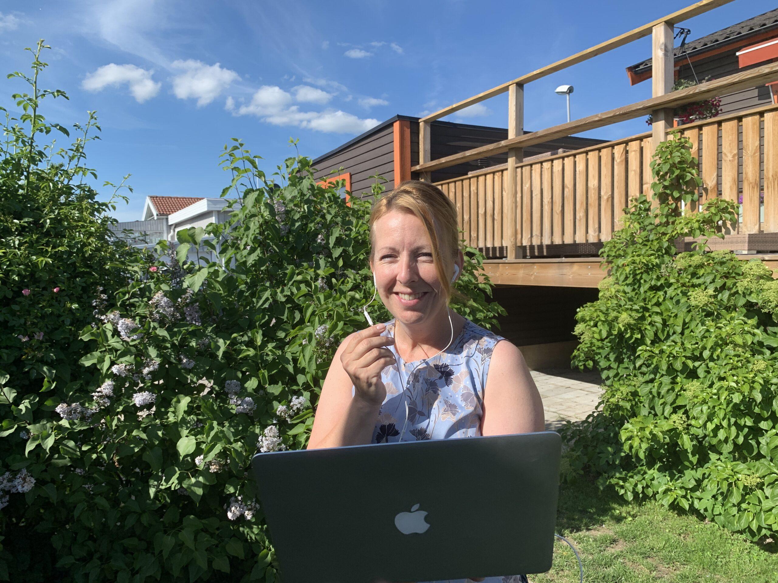 Malin står i en grönskande trädgård med laptop i handen och pratar i sitt headset.